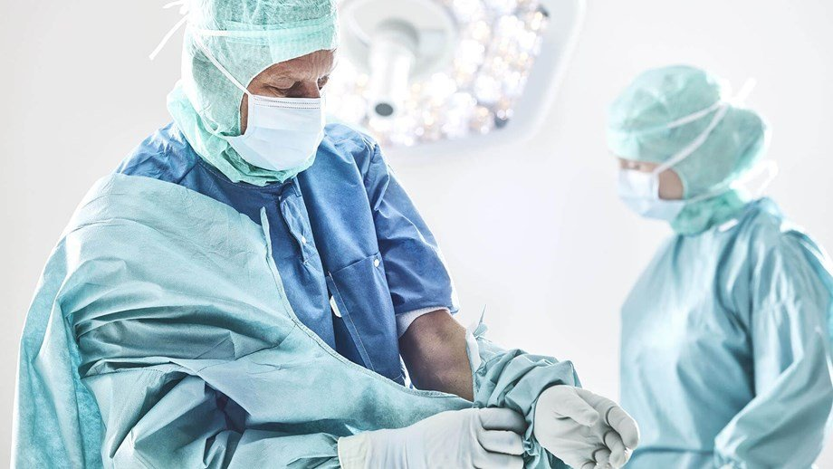 Surgeon undonning his gown